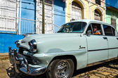 American car cruising on colonial streets — Stock Photo
