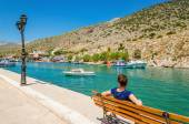 Young lady in blue sitting on bench, Greece — Stock Photo
