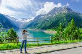 Young woman photographing alpine lake, Austria — Stock Photo