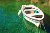 Empty white boat floating in clear water — Stock Photo