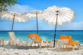 White sunbeds and orange towels on sandy beach — Stock Photo