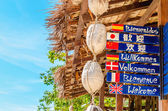 Welcome sign in different languages on beach — Stock Photo