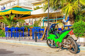 Green motorbike in front of Greek restaurant  — Stock Photo
