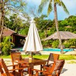 Table with sun umbrella on exotic beach — Stock Photo #74295471