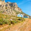 Greek landscape, hills, blue and white church — Stock Photo #75963707