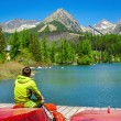 Young man at pier mountain lake with high peaks — Stock Photo #76907101