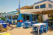 Blue wooden tables and chairs in Greek restaurant — Stock Photo