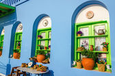 Colorful Greek restaurant with typical blue wall — Stock Photo