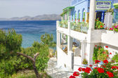 Panoramic typical Greek restaurant with flowers — Stock Photo