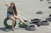 The girl in a beautiful dress sits on a wheel — Stock Photo