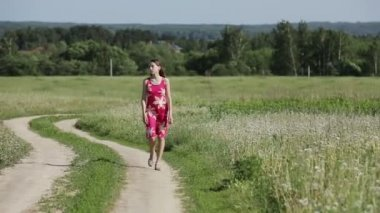 Girl walking by road in field — Stock video