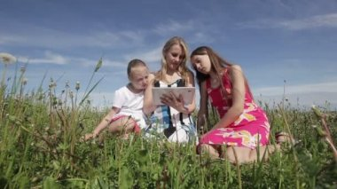 Woman and daughter using tablet computer in field — Stock Video