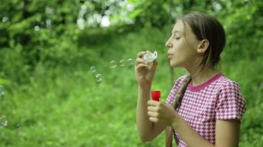 Young girl blowing soap bubbles outdoor — Stock Video