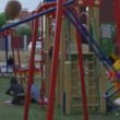 Children Are at the Playground at the Yard, Playing, Boys are Swinging on a Swings — Stock Video #79400166