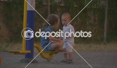 Little girl in blue and little boy in white together on playground — Stock Video