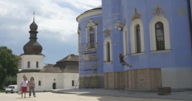 Blue Walls of St. Michael's Cathedral, Repair, Restorers, Men, Industrial Climbers, People are Passing by, White Church on Background — Stock Video