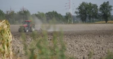 Tractor Distantly Tractor is Plowing The Field Flying Dust Cars are Passing by the Road along the Field High-Voltage Tower Blurred Image Branches — Стоковое видео