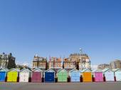 Brightly colored beach huts lined up along the beach with traditional architecture behind, under clear blue sky. — Stock Photo