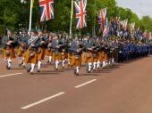 London, UK, parade of uniformed pipers along the Mall under the Union Jack flags. — Stock Photo