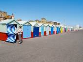 Couple put their wind protection up outside their beach hut at Hove. — Stock Photo