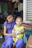 Young Asian woman with thanaka on face holding baby on lap Myanmar Travel Images — Stock Photo