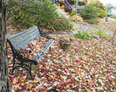 Garden bench seat hit by autumn leaf fall. — Stock Photo