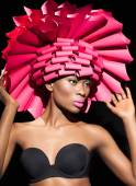 Beauty portrait closeup of a black young girl in pink hat and black bustiers. — Stock Photo