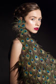 Fashion glamour portrait go young beautiful model with peacock feathers on her head. — Stock Photo
