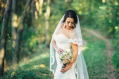 Beautiful bride outdoors in a forest — Stock Photo