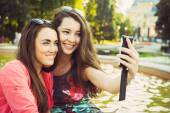 Two young women taking a selfie outdoors — Stock Photo