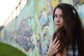 Portrait of young woman sitting at graffiti wall — Stock Photo