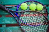 Tennis racket with balls on tennis court — Stock Photo
