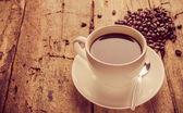Šálek kávy na dřevěný stůl, vintage barvu — Stock fotografie
