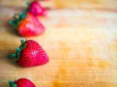 Rij van aardbeien op een houten bord met lege ruimte — Stockfoto