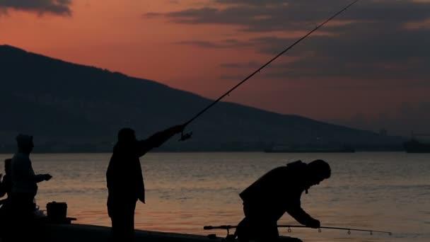 Silhouette fisherman throws fishing tackles at morning — Vidéo