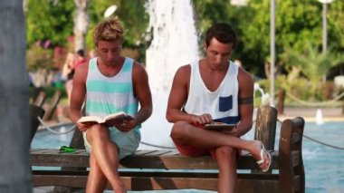Two young man sitting at the park and relaxing — Vídeo de Stock
