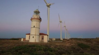 Wind turbines generating clean power with lighthouse at sunset time, blue hours — Stock Video