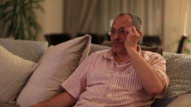 Uomo di mezza età guardando la televisione e lo zapping di canale — Video Stock