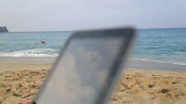 Mani della donna che tiene compressa digitale sulla spiaggia — Video Stock