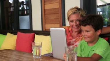 Mother and son with digital tablet at cafe — Stock Video