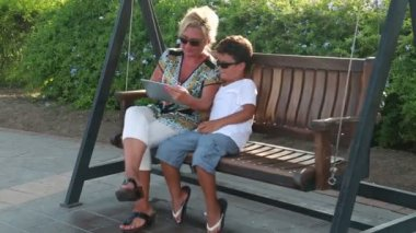 Mother and son swinging and using digital tablet 3 — 图库视频影像