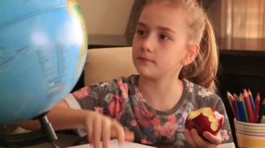 Little girl study at home and eating apple — Stock Video