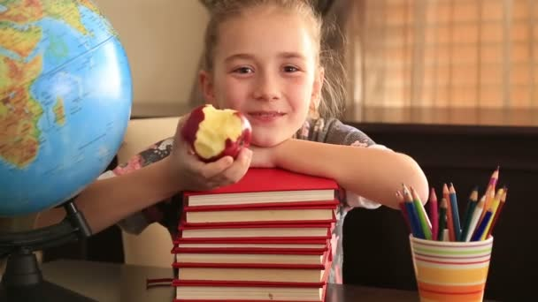 Elementary age girl posing on a stack of books. — Vidéo