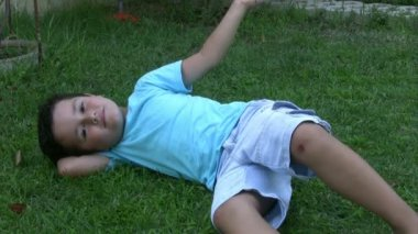 Little boy relaxing in the garden — Stock Video