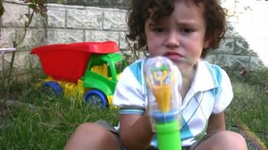 Happy child blowing bubbles in the garden — Stock Video