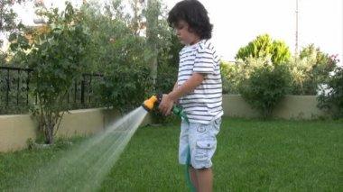 Little boy watering garden — Stockvideo