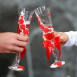 Unusual and original Wedding glasses decorated with roses. Bride and groom holding champagne glasses. Champagne Toast . Wedding glasses in their hands in selective focus. Backyard party background. — Stock Photo #77474224