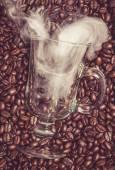 Irish coffee glass with smoke in coffee beans — Stock Photo