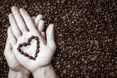 Coffee beans heart symbol on top of the hand — Stock Photo