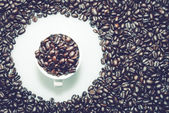 Coffee beans texture with a coffe cup in a circle. — Stock Photo